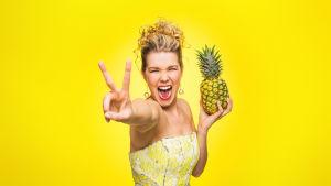 Tuija Pehkonen keltaisessa tilassa ananas kädessään.