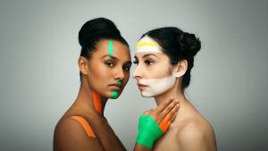 Kaksi naista ovat kasvot vastakkain. Vasemman puolinen tummaihoinen katsoo kameraan. Oikean puolinen tummatukkainen vaaleaihoinen katsoo vasemmalle.