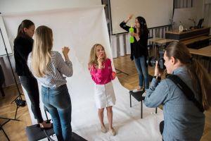 Fotografering i studio. En fotograf tar ett foto av en kvinna som står framför en vit skärm, hon blåser såpbubblor. Runt henne står tre personer som också blåser bubblor.