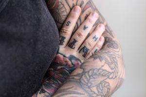 Lähikuva Natalia Tolmatsovan tatuoiduista käsivarsista.