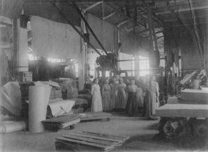 Kvinnliga arbetare i ljus klänningar i Valkeakoski pappersfabrik i början av 1900-talet.