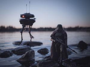 En leksaksfigur föreställande en soldat från Star wars. Den står på en sten vid en strandkant. I bakgrunden syns också en robot från Star wars.