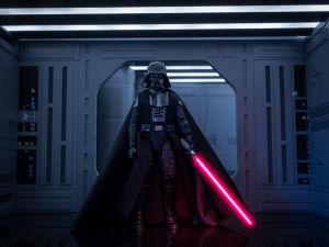 En leksaksfigur föreställande Darth Vader från Star wars. Han står framför en port, ser ut att vara en rymdbas. Han håller sin röda ljussabel i handen.