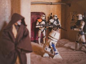 Leksaksfigurer föreställande soldater från Star wars, samt en robot och Obi Wan Kenobi. Soldaterna vaktar en dörr och Obi Wan gömmer sig i förgrunden.