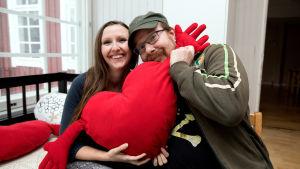 Två skådespelare kramar samma stora röda hjärta.