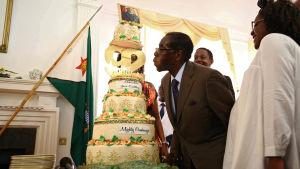 Zimbabwes president Robert Mugabe blåser ut ljusen på en födelsedagstårta den 22 februari i Harare.