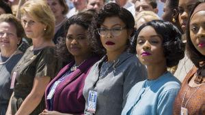 De svarta kvinnorna står på rad för att ta emot de vita astronauterna.