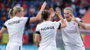 Vitklädda norska damfotbollspelare gör high-five.