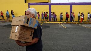 Folk står i kö för att få matlådor i Puerto Rico.