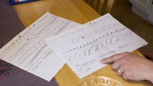 Två papper som är skrivövningar som Sabina gjort. Den ena, som hon gjorde när hon var ganska dålig, är hackig och vinglig.