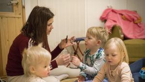 En kvinna leker med tre barn.