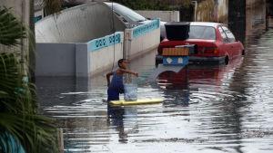 Pojke leker i vattenmassor på en översvämmad gata i Toa Baja i Puerto Rico.
