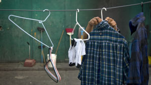 En hemlös man hänger upp sina kläder på tork en bakgård.