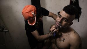 Turvapaikanhakija ajaa partaa höylällä toiselta turvapaikanhakijalta