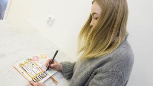Caroline Eriksson har långt blont hår och en grå tröja. Hon lutar sig över ett bord med ett häfte framför sig. I handen håller hon en penna och hon ritar en bokhylla i häftet.