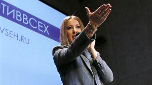 Ksenia Sobtjak står på en scen och talar.