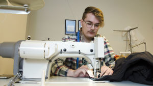 Anton West sitter bakom en industrisymaskin och syr i en dragkedja.