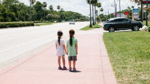 Två flickor står ensamma på gatan.