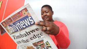 Kvinna läser tidning i Zimbabwe