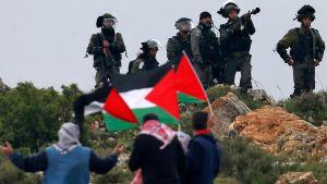 Palestinska flaggor framför israelisk militär under demonstration i Qusra på Västbanken 30.3.2018.