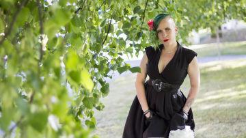 En kvinna med grönt hår och rött läppstift, iklädd en svart klänning, står bland gröna lövträd.