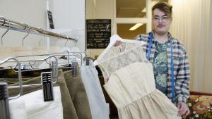 Anton West håller upp en vit klänning som han designat och sytt av gamla tyger.
