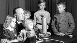 Lastentunti ja Markus-setä sekä lapsia, Annikki Väänäsen lapsiryhmä ja Kalevi Koski seisomassa oikealla
