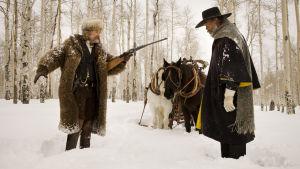 Mies osoittaa toista kiväärillä lumisessa metsässä.