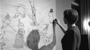 Tove Jansson piirtää muumihahmoja