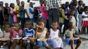 Haitiska barn sitter och äter