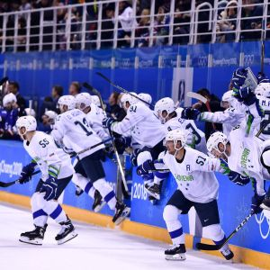 Sloveniens hockeylandslag rusar ut ur spelarbåset för att fira seger.