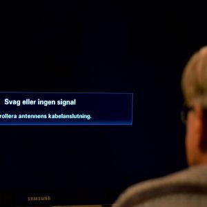 """En man tittar på en tv där det på skärmen står """"Svag eller ingen signal""""."""