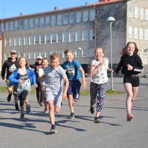 Elever som springer på en skolgård.