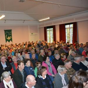 Många människor sitter bänkade i en sal.
