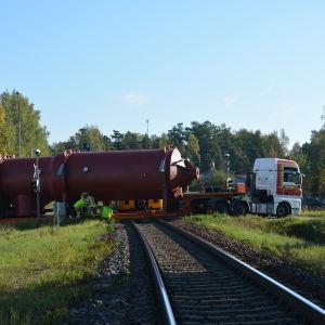 En långtradare står rakt över en järnvägsövergång. Två brandmän står vid ena sidan av fordonet.