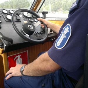 En polis sitter och rattar en båt.