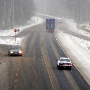 Bilar kör på en väg som är täcks med slask. Snön yr.