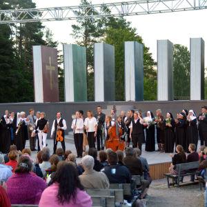 Skådespelare och musiker står på rad på en scen. Publiken applåderar.