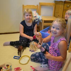 Flickor leker med dockor och hästar.