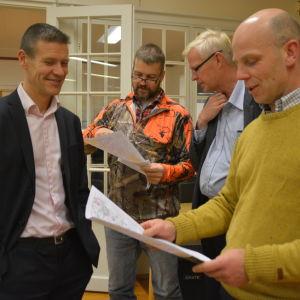 Herkko Plit, vd för Baltic Connector, tittar på Kristian Westerholm karta. Jan Wasström visar en karta åt Tom Främling från Baltic Connector.