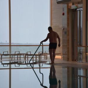 En man går i en tom simbassäng.