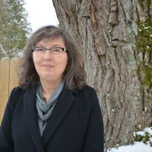 En kvinna i svart jacka står ute vid en ek. Hon heter Tina Nordman.