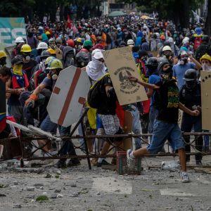 Demonstranter med skyltar fyller en gata i staden Caracas, Venezuela, den 22 juli 2017.