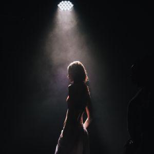 en kvinna står på scenen i strålkastarljus