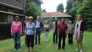 Joukko ihmisiä seisoo talon vieressä nurmikolla