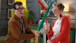 två personer leker med sopborste och paraply
