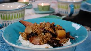 Portion med långbakad frukt och mysli på yogurt.