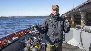 En ung man, kaptenlöjtnant, som står i en båt.