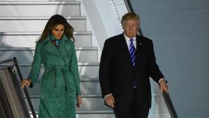 USA:s president Donald Trump går ner för ett flygplans trappor tillsammans med frun Melania Trump.