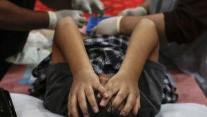 Pojke blir omskuren i Malaysia.